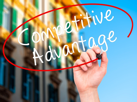correlate: Man Hand writing Competitive Advantage with black marker on visual screen. Isolated on city. Business, technology, internet concept. Stock Image