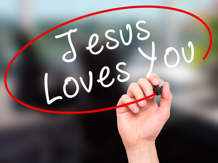 testament schreiben: Man Hand writing Jesus Loves You with black marker on visual screen. Isolated on office. Religion, technology, internet concept. Stock Image