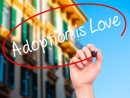 daughter in law: Man Hand writing Adoption is Love with black marker on visual screen. Isolated on city. Adoption, technology, internet concept. Stock Photo