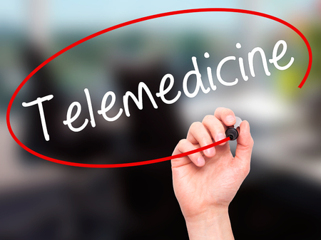 Man Hand writing Telemedicine with black marker on visual screen. Isolated on office. Business, technology, internet concept. Stock Image