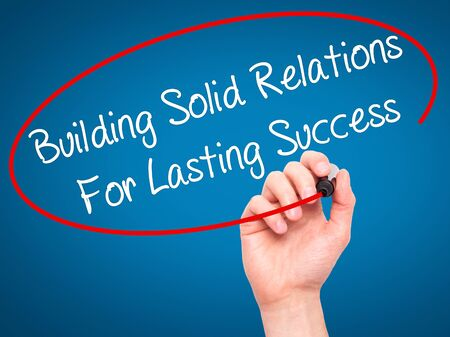 lasting: Man Hand writing Building Solid Relations For Lasting Success with black marker on visual screen. Isolated on blue. Business, technology, internet concept. Stock Image