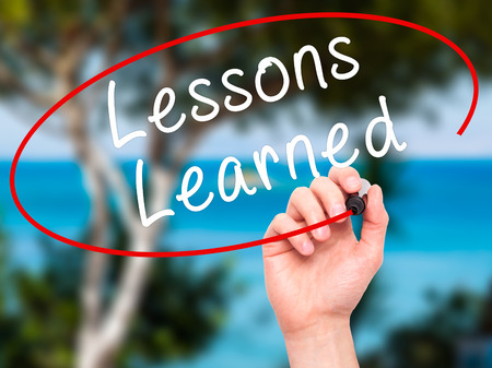 recap: Man Hand writing Lessons Learned with black marker on visual screen. Isolated on nature. Business, technology, internet concept. Stock Image