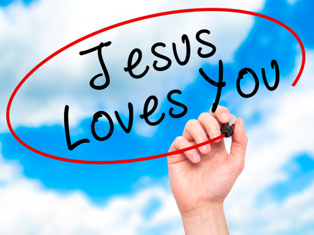 testament schreiben: Man Hand writing Jesus Loves You with black marker on visual screen. Isolated on sky. Religion, technology, internet concept. Stock Image Lizenzfreie Bilder