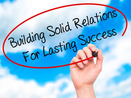 lasting: Man Hand writing Building Solid Relations For Lasting Success with black marker on visual screen. Isolated on sky. Business, technology, internet concept. Stock Image Stock Photo