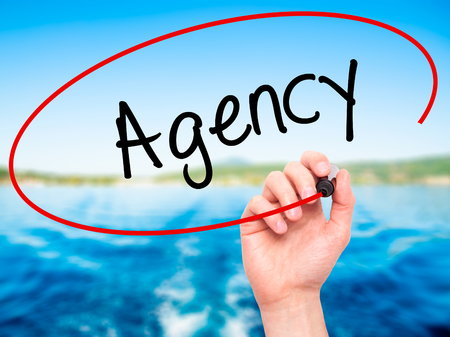 stock agency: Man Hand writing Agency with black marker on visual screen. Isolated on nature. Business, technology, internet concept. Stock Photo