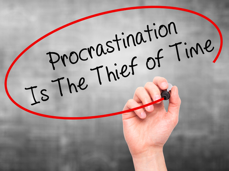 procrastination: Man Hand writing  Procrastination Is The Thief of Time with black marker on visual screen. Isolated on grey. Business, technology, internet concept. Stock Image