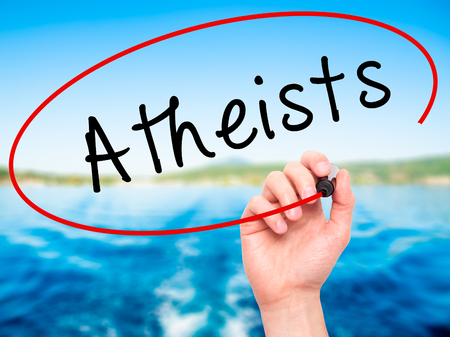 disbelieve: Man Hand writing Atheists with black marker on visual screen. Isolated on nature. Business, technology, internet concept. Stock Image
