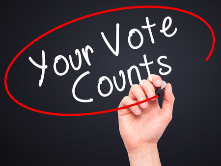counts: Man Hand writing Your Vote Counts with black marker on visual screen. Isolated on black. Business, technology, internet concept. Stock Image