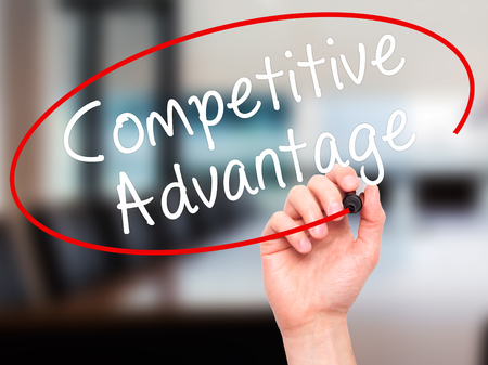 correlate: Man Hand writing Competitive Advantage with black marker on visual screen. Isolated on office. Business, technology, internet concept. Stock Image