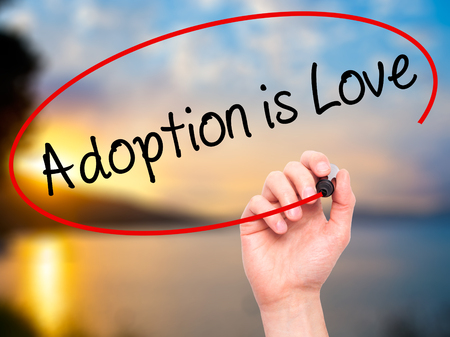 adoption: Man Hand writing Adoption is Love with black marker on visual screen. Isolated on nature. Adoption, technology, internet concept. Stock Photo Stock Photo