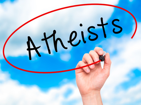 disbelieve: Man Hand writing Atheists with black marker on visual screen. Isolated on sky. Business, technology, internet concept. Stock Image