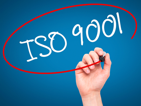 standardization: Man Hand writing  Iso 9001 with black marker on visual screen. Isolated on blue. Business, technology, internet concept. Stock Photo Stock Photo