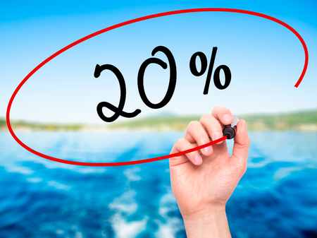 Man Hand writing 20% with black marker on visual screen. Isolated on nature. Business, technology, internet concept. Stock Photo