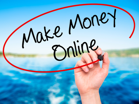 financial advisors: Man Hand writing  Make Money Online  with black marker on visual screen. Isolated on nature. Business, technology, internet concept. Stock Photo