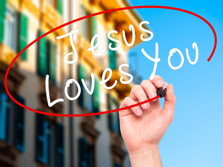 testament schreiben: Man Hand writing Jesus Loves You with black marker on visual screen. Isolated on city. Religion, technology, internet concept. Stock Image
