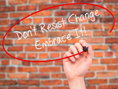 resist: Man Hand writing Dont Resist Change, Embrace It! with black marker on visual screen. Isolated on bricks. Business, technology, internet concept.