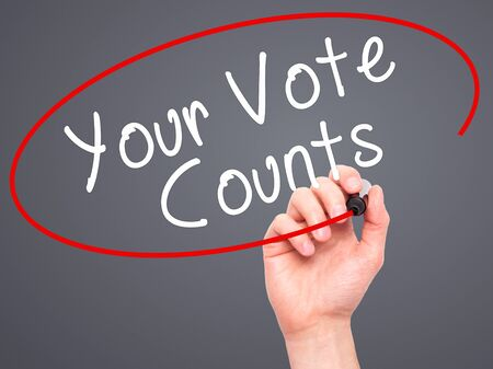 libertarian: Man Hand writing Your Vote Counts with black marker on visual screen. Isolated on grey. Business, technology, internet concept. Stock Image