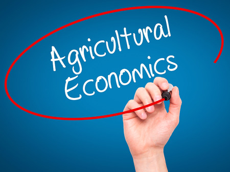 Man Hand writing Agricultural Economics with black marker on visual screen. Isolated on blue. Business, technology, internet concept. Stock Photo Stock Photo