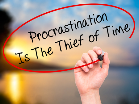 procrastination: Man Hand writing  Procrastination Is The Thief of Time with black marker on visual screen. Isolated on nature. Business, technology, internet concept. Stock Image Stock Photo