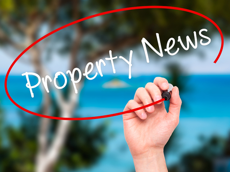 press agent: Man Hand writing Property News with black marker on visual screen. Isolated on nature. Business, technology, internet concept. Stock Image Stock Photo