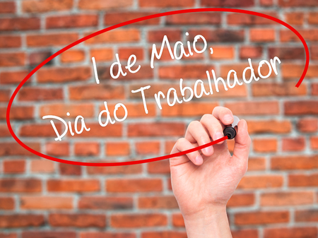 Man Hand writing 1 de Maio, Dia do Trabalhador (In Portuguese: 1 May, Labor Day) with black marker on visual screen. Isolated on bricks. Business, technology, internet concept. Stock Photo 版權商用圖片