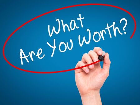 rewarding: Man Hand writing What Are You Worth? with black marker on visual screen. Isolated on blue. Business, technology, internet concept. Stock Image