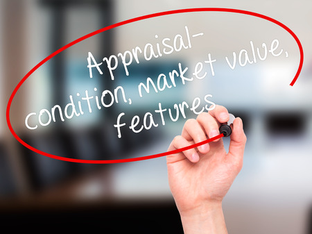 Man Hand writing Appraisal - condition, market value, features, with black marker on visual screen. Isolated on office. Business, technology, internet concept. Stock Image