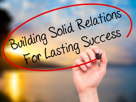 lasting: Man Hand writing Building Solid Relations For Lasting Success with black marker on visual screen. Isolated on nature. Business, technology, internet concept. Stock Image