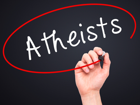 heathen: Man Hand writing Atheists with black marker on visual screen. Isolated on black. Business, technology, internet concept. Stock Image