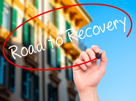 road to recovery: Man Hand writing Road to Recovery with black marker on visual screen. Isolated on city. Business, technology, internet concept. Stock Image