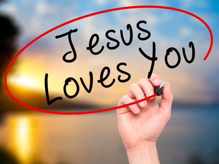 jesus word: Man Hand writing Jesus Loves You with black marker on visual screen. Isolated on nature. Religion, technology, internet concept. Stock Image