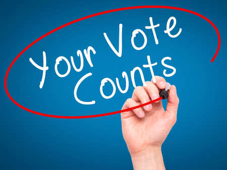 libertarian: Man Hand writing Your Vote Counts with black marker on visual screen. Isolated on blue. Business, technology, internet concept. Stock Image