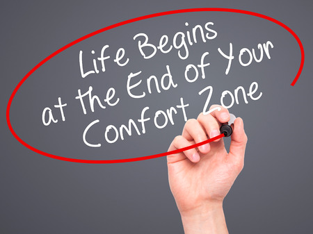 begins: Man Hand writing Life Begins at the End of Your Comfort Zone with black marker on visual screen. Isolated on grey. Business, technology, internet concept. Stock Image