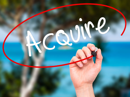 acquiring: Man Hand writing Acquire with black marker on visual screen. Isolated on background. Business, technology, internet concept. Stock Photo