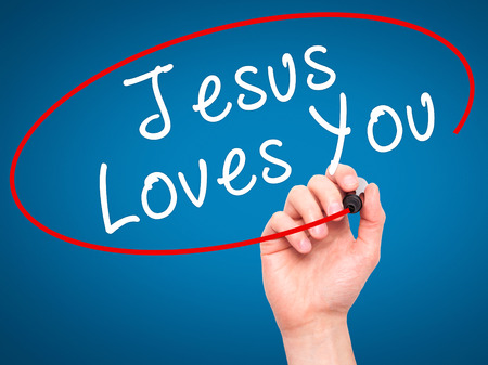 testament schreiben: Man Hand writing Jesus Loves You with black marker on visual screen. Isolated on blue. Religion, technology, internet concept. Stock Image