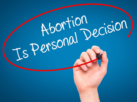 abortion: Man Hand writing Abortion Is Personal Decision with black marker on visual screen. Isolated on blue. Business, technology, internet concept. Stock Photo Stock Photo