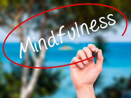 open minded: Man Hand writing Mindfulness  with black marker on visual screen. Isolated on nature. Business, technology, internet concept. Stock Image