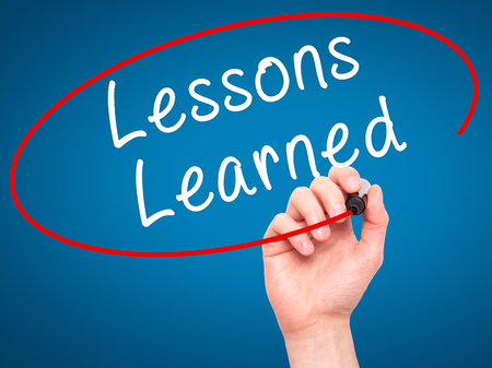 summarize: Man Hand writing Lessons Learned with black marker on visual screen. Isolated on blue. Business, technology, internet concept. Stock Image