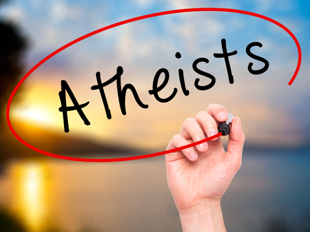 atheism: Man Hand writing Atheists with black marker on visual screen. Isolated on nature. Business, technology, internet concept. Stock Image