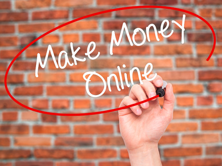 writing on screen: Man Hand writing  Make Money Online  with black marker on visual screen. Isolated on bricks. Business, technology, internet concept. Stock Photo