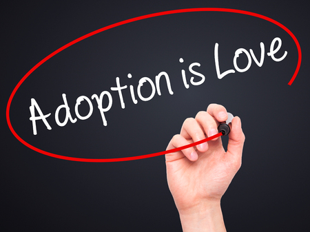 foster parenting: Man Hand writing Adoption is Love with black marker on visual screen. Isolated on black. Adoption, technology, internet concept. Stock Photo