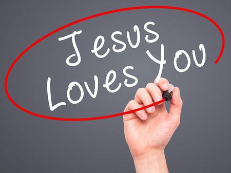 testament schreiben: Man Hand writing Jesus Loves You with black marker on visual screen. Isolated on grey. Religion, technology, internet concept. Stock Image Lizenzfreie Bilder