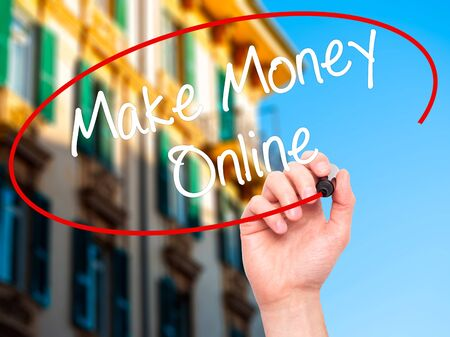 financial advisors: Man Hand writing  Make Money Online  with black marker on visual screen. Isolated on city. Business, technology, internet concept. Stock Photo