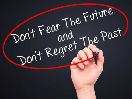 regret: Man Hand writing Dont Fear The Future and Dont Regret The Past with black marker on visual screen. Isolated on black. Life, technology, internet concept. Stock Image Stock Photo