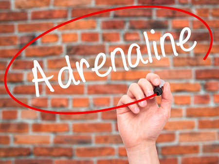 adrenaline: Man Hand writing Adrenaline  with black marker on visual screen. Isolated on bricks. Business, technology, internet concept. Stock Photo
