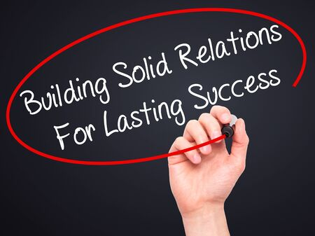 lasting: Man Hand writing Building Solid Relations For Lasting Success with black marker on visual screen. Isolated on black. Business, technology, internet concept. Stock Image Stock Photo