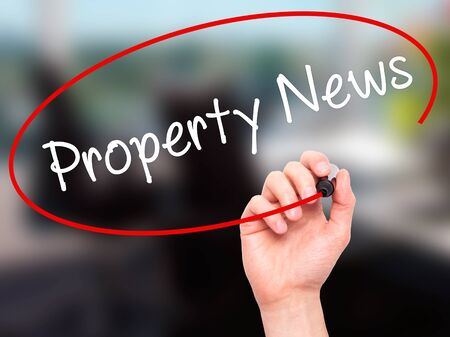 press agent: Man Hand writing Property News with black marker on visual screen. Isolated on office. Business, technology, internet concept. Stock Image Stock Photo