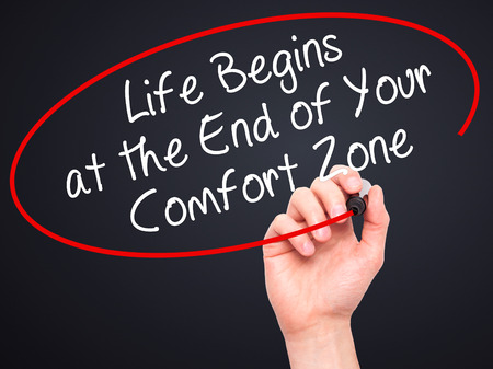 begins: Man Hand writing Life Begins at the End of Your Comfort Zone with black marker on visual screen. Isolated on black. Business, technology, internet concept. Stock Image