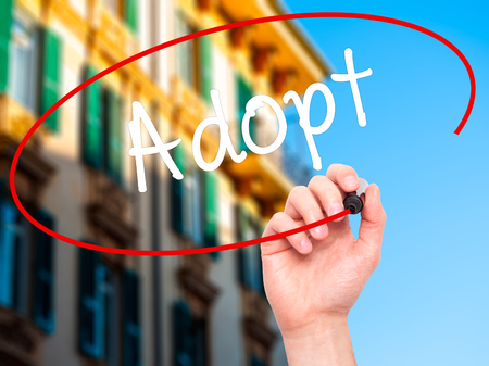 adopting: Man Hand writing Adopt  with black marker on visual screen. Isolated on city. Business, technology, internet concept. Stock Photo Stock Photo
