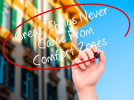 self discovery: Man Hand writing Great Things Never Came From Comfort Zones with black marker on visual screen. Isolated on city. Business, technology, internet concept. Stock Image